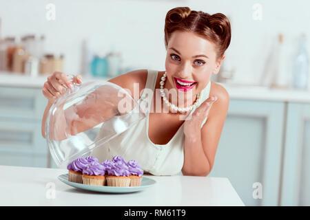 Smiling pin up girl demonstrating plate full of homemade cupcakes - Stock Photo