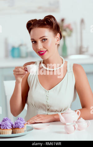 Elegant pin up girl in pearl necklace drinking coffee near plate of cupcakes - Stock Photo