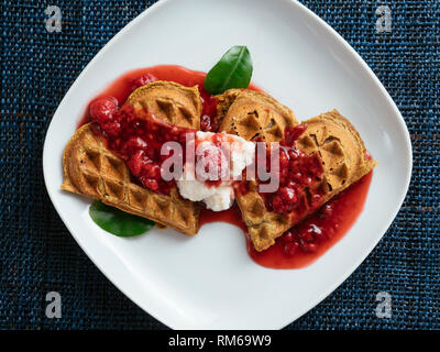 Heart shaped vegan beet waffles with a raspberry sauce. - Stock Photo