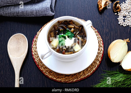 Homemade vegetarian mushroom soup with pearl barley and vegetables in a white Cup with two handles. Dill, parsley and onions close-up. - Stock Photo