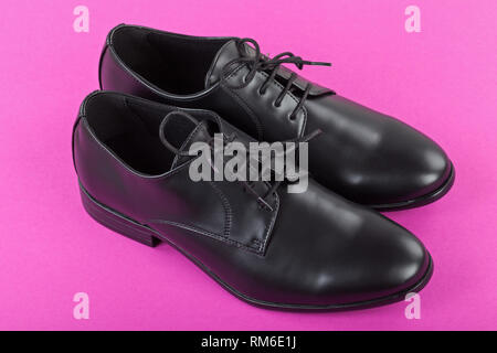 Close up picture of mens footwear Black leather elegant shoes on pink background - Stock Photo