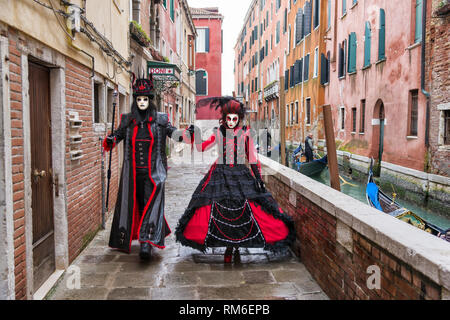 Two Posers walking beside a canal in Venice. They are participants in the Italian Venice Carnival. - Stock Photo