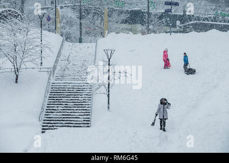 MOSCOW, RUSSIA - FEBRUARY 13, 2019: Boy and girl snow tubing a snowfall. - Stock Photo