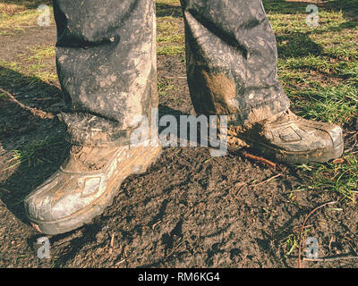 Farmer wearing muddy boots in daily business. Muddy rubber boot in horse farm area - Stock Photo