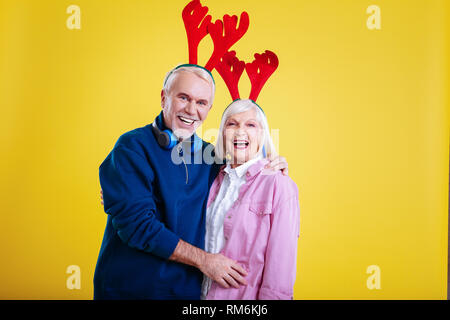 Cheerful retired man and woman wearing funny head bands - Stock Photo