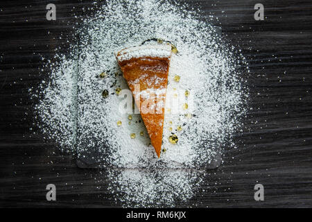 One slice of cheesecake covered with powdered sugar and poured with honey - Stock Photo