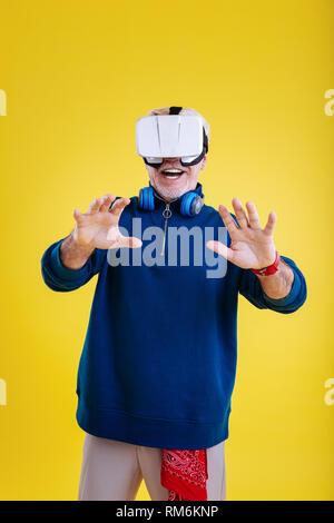 Stylish retired man wearing beige trousers wearing VR glasses - Stock Photo