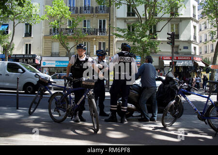 Bicycle-mounted French Police Officers speak to man with motorcycle, boulevard Barbès, 75018, Paris - Stock Photo