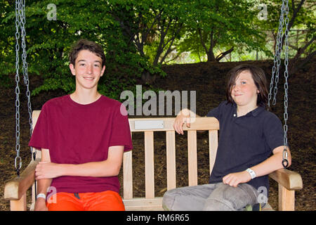 2 teen boys; wood seat swing; friends; woods; smiling; happy; relaxing, wrist bands, horizontal; MR - Stock Photo