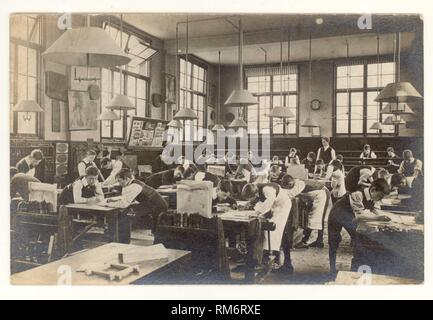 Edwardian postcard of boys drawing plans for woodwork, carpentry in a classroom, circa 1910, U.K. - Stock Photo