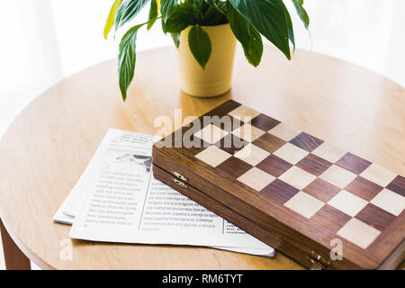 wooden chess board near newspaper and plant on coffee table