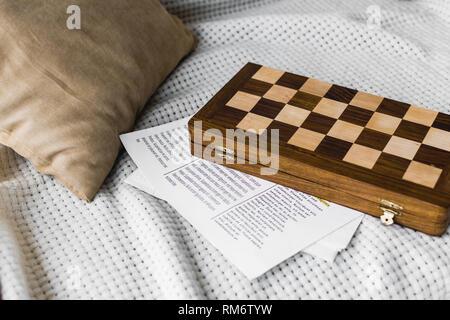 wooden chess board near newspaper on sofa