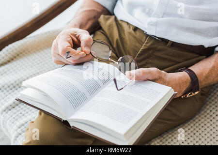 cropped view of senior man reading book and holding glasses at home - Stock Photo