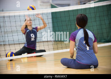 Sports for disabled people. Training. Two young women sitting on the floor and playing volleyball. Stock Photo