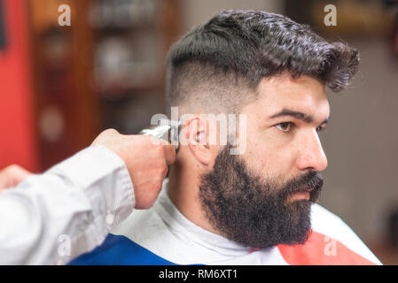 Handsome bearded man, getting haircut by barber, with electric trimmer at barbershop . - Stock Photo