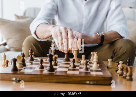 cropped view of retired man with playing chess at home
