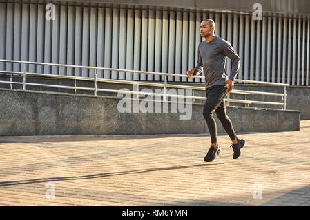 He is always in good shape Full length portrait of strong and athletic african man enjoying his cardio training in one sunny morning. Side view. Side view. Healthy lifestyle. Sport and motivation concept. - Stock Photo