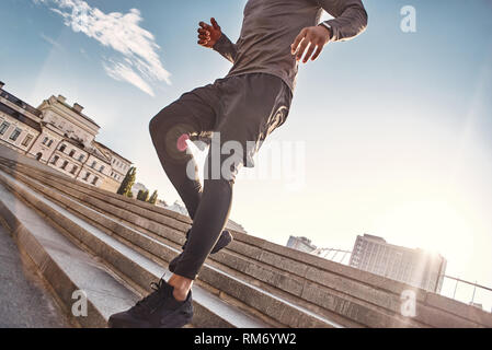 He is always in a good shape Cut view of athletic african man in sportswear jogging down stairs on the sunny morning. Healthy lifestyle. Sport and motivation concept. Urban workout - Stock Photo