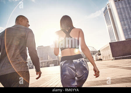 That was great workout Back view of young multiracial couple in fitness clothes going home after morning training together. Common hobbies. Healthy couple. Sport motivation concept. Fitness concept. Women beauty. Healthy life. Exercising together. Active morning. - Stock Photo