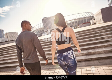 After great workout. Back view of young multiracial couple in fitness clothes going home after active training together. Urban environment. Healthy couple. Sport motivation concept. Fitness concept. Women beauty. Healthy life. Exercising together. Active morning. Common hobbies - Stock Photo