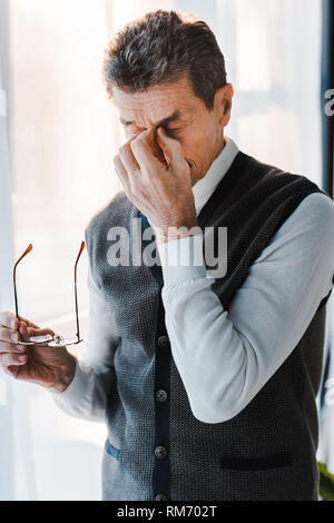tired senior man with grey hair touching eyes while holding glasses - Stock Photo