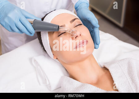 beautician doing physiotherapy whith darsonvalization equipment on woman face at beauty salon - Stock Photo