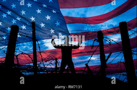 Man looking through barbed wire/razor wire fence with USA stars and stripes flag in background. Immigration, border fence, Mexican border... concept - Stock Photo