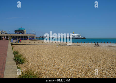 Eastbourne, Sussex, England, UK - August 1, 2018: View of the pier from the promenade with the art deco bandstand.   Two empty deckchairs are open on  - Stock Photo