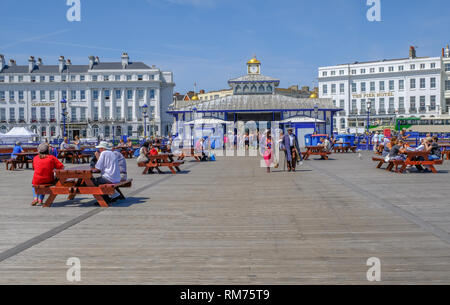 Eastbourne, Sussex, England, UK - August 1, 2018: People strolling and sitting on picnic benches near the entrance of the Pier in Eastbourne.  The Cla - Stock Photo