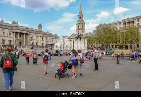 Trafalgar Square, London, England, UK - April 22, 2018: View of the Trafalgar Square with lots of tourists and visitors looking towards the National P - Stock Photo