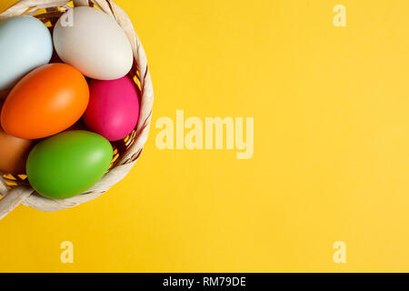 Easter basket filled with colorful eggs on a yellow background - Stock Photo
