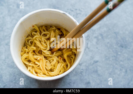 Instant Curry Flavored Ramen Noodles served with Chopsticks. in Plastic Cup. Traditional Fast Food. - Stock Photo