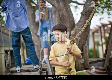Smiling young boy holding on to a rope swing while playing with friends in the back yard. - Stock Photo