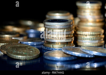 Many euro coins stacked on black background. - Stock Photo