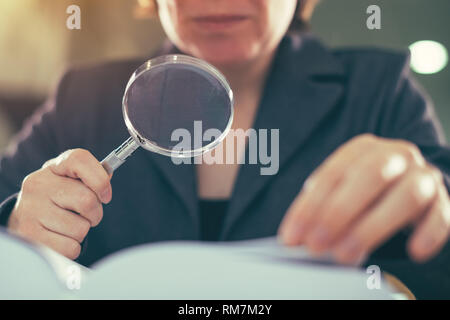 Business corruption audit inspection concept, female inspector using magnifying glass - Stock Photo