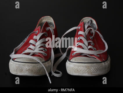 Close up of pair of sneakers - red and white vintage worn out shoes - youth hipster shoes on black background - Stock Photo