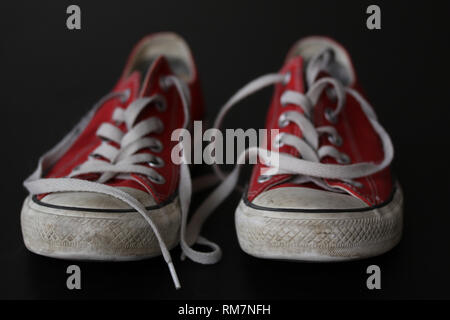 Close up of pair of sneakers - red and white vintage worn out shoes - youth hipster shoes on black background with select focus. - Stock Photo