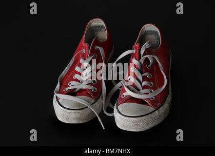 Close up of pair of sneakers - red and white vintage worn out shoes - youth hipster shoes on black background - top view - Stock Photo