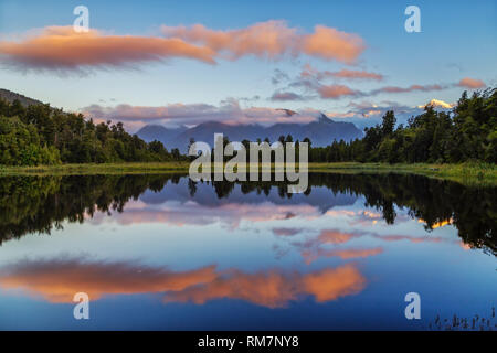 Lake Matheson is famous for the fact that seen from the northwest Aoraki/Mount Cook and Mount Tasman are reflected on the water surface. - Stock Photo
