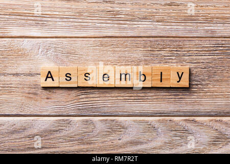 ASSEMBLY word written on wood block. ASSEMBLY text on wooden table for your desing, concept. - Stock Photo