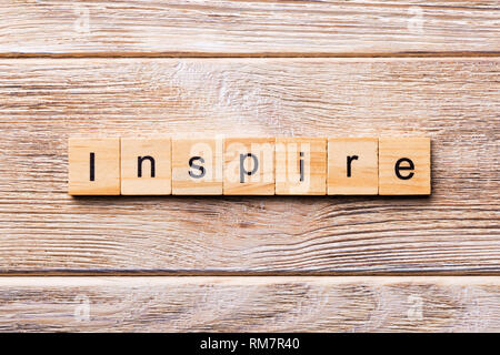 Inspire word written on wood block. Inspire text on wooden table for your desing, concept. - Stock Photo
