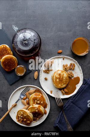 Festive composition with pancakes and condensed caramel milk at black background. Concept of festive shrove food. Breakfast for two - Stock Photo
