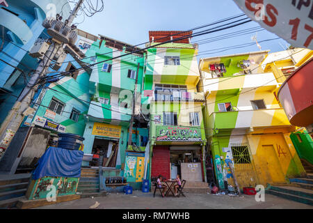 Colourful main square of the favela Santa Marta (Dona Marta) in Rio de Janeiro with two girls sitting at a table in front of a bar - Stock Photo