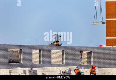 View of Construction Site With Workers Laying Bricks and Preparing Cement. Blue Sky and Unfinished Apartment Building Background. - Stock Photo