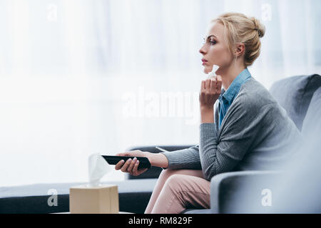 upset woman with tissue watching tv on couch at home alone - Stock Photo