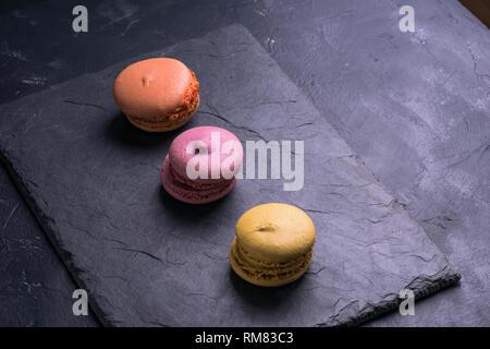 Photo in a dark key French sweet multi-colored macaroni - Stock Photo