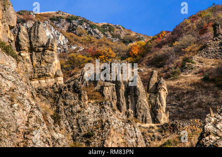 Varicolored autumn slopes with sharp stone ledges in the mountains of Geghama ridge,on a sunny day around Geghard monastery in Armenia - Stock Photo