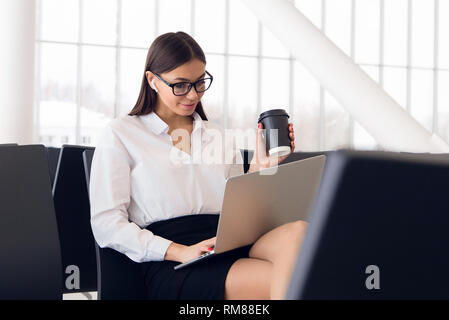 Breaktime business. Beautiful business woman working on laptop while waiting for her flight in an airport - Stock Photo