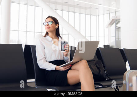 Female executive with suitcase in work related business trip waiting for her flight in an airport - Stock Photo