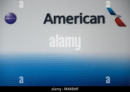 American Airlines corporate logo with One World airline partnership globe icon to the left. - Stock Photo